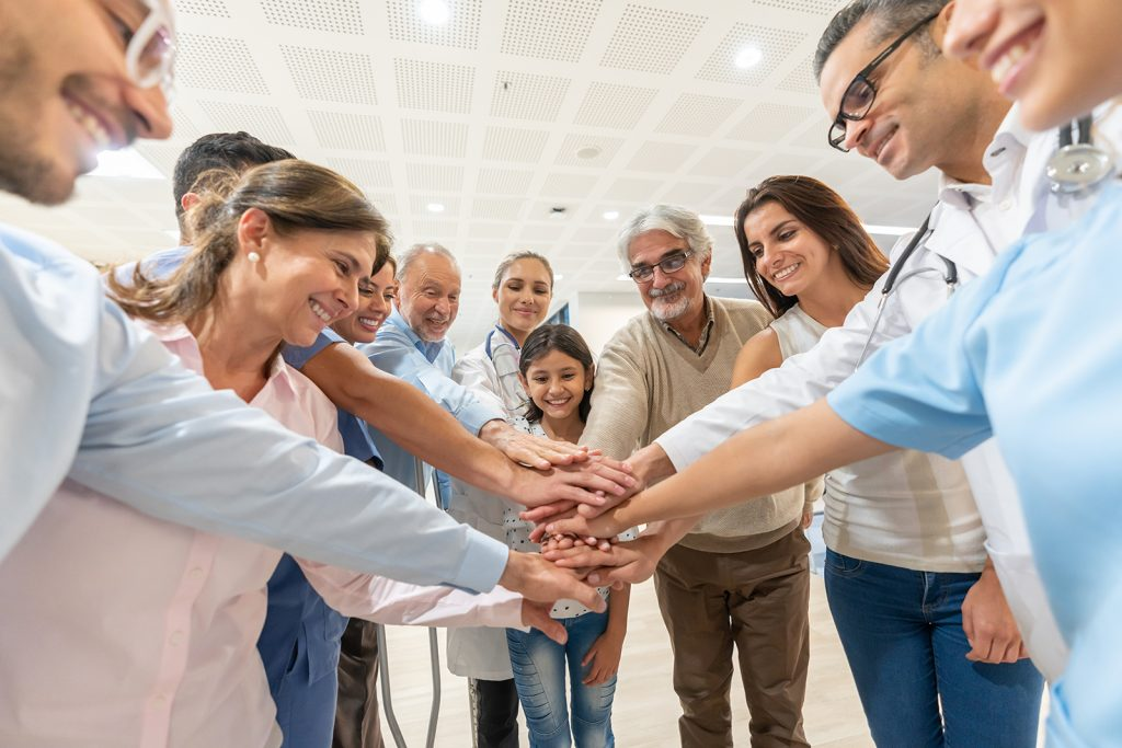 Group of healthcare workers and patients of different ages in a huddle all with hands in smiling