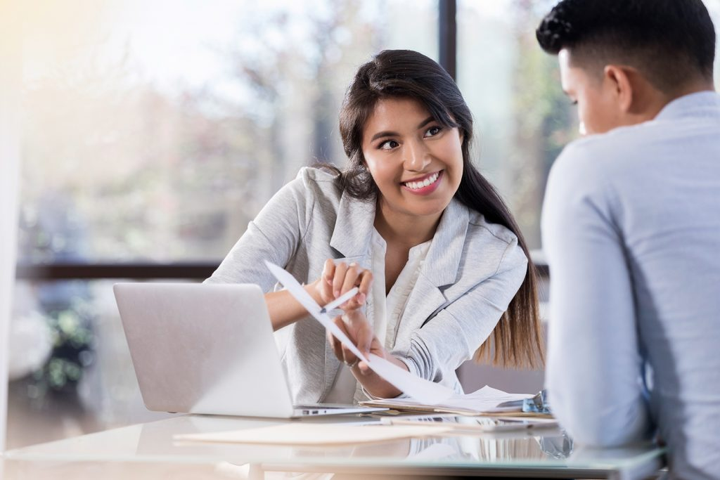 Businesswoman discusses document with colleague