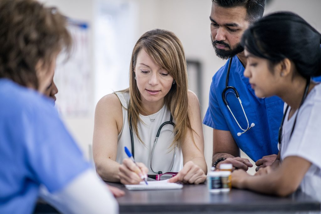 A multi-ethnic group of doctors are indoors in an office. They are gathered around a table for a meeting. One woman is taking notes.