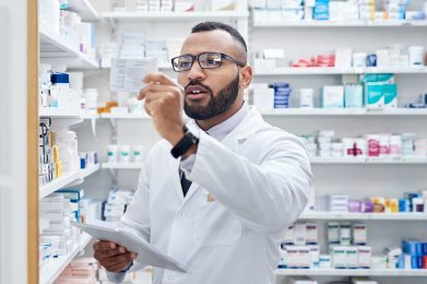 young pharmacist working on a digital tablet inside of a pharmacy during the day
