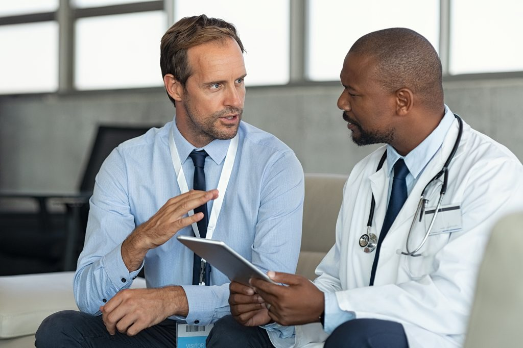 Pharmaceutical representative talking with doctor sitting on couch. African mature practitioner discussing results of the analysis with specialist while consulting diagnosis on digital tablet. Doctor in conversation with medical advisor in hospital room discussing patients report case.
