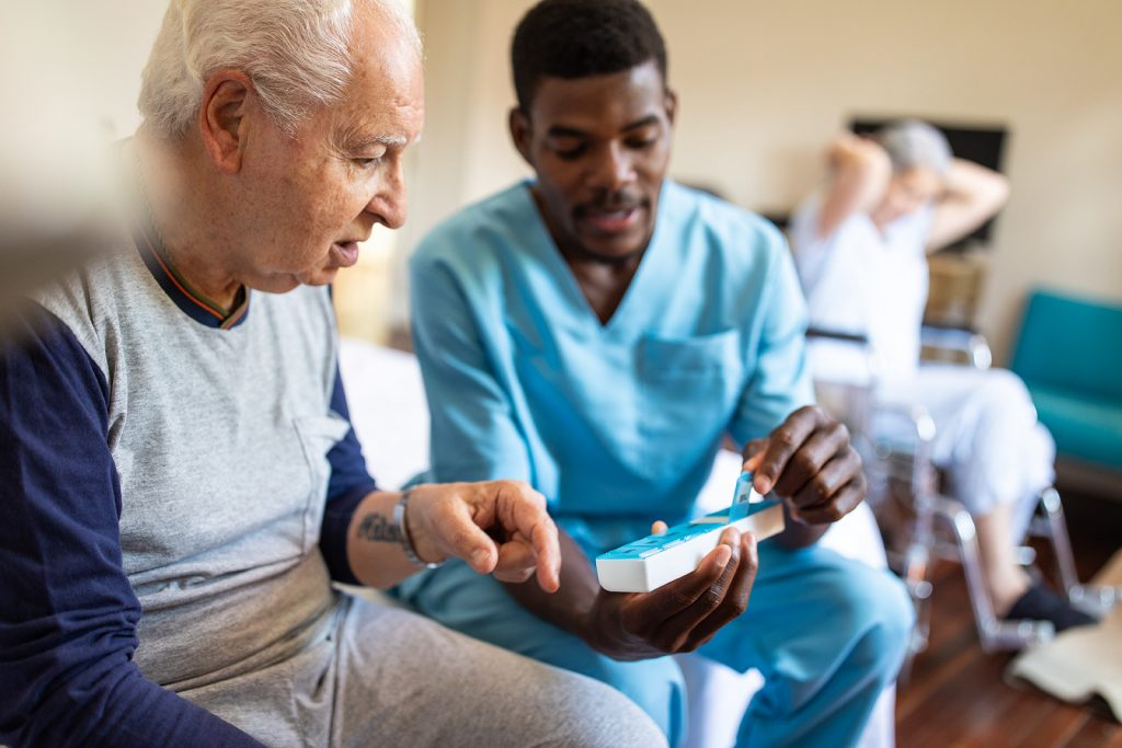 Black male nurse sitting on bed and giving instructions to senior patient when to take his pills in nursing home