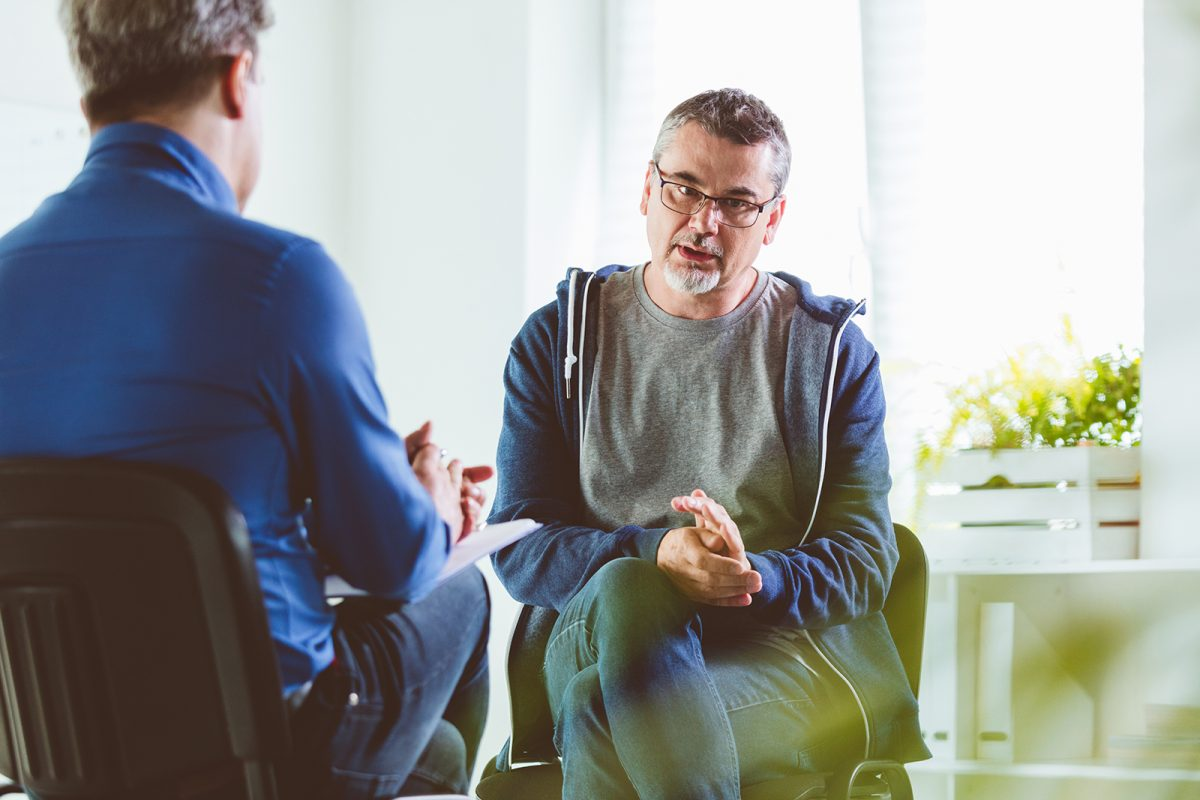 Mature psychotherapist talking with depressed man. Coach is discussing about mental illness with man. They are in meeting in psychotherapeutic office